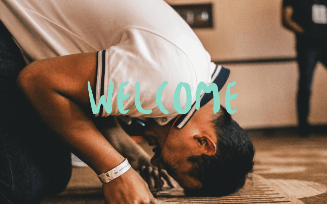 """Decorative image of man touching his head to the ground with """"Welcome"""" text"""